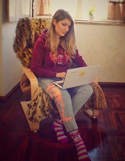 Estudiar un master online - Miss May Paris estudiando, sentada en una silla con un portátil